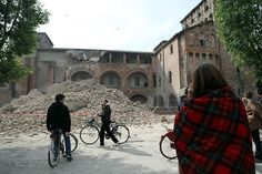 A woman stands with a blanket on her shoulders to take in the scale of earthquake damage near the Castello delle Rocche in Finale Emilia, a municipality in the province of Modena