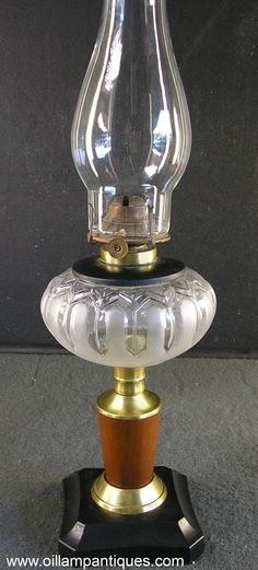 """The lovely tapered timber stem of this oil lamp sets it apart from other composite kerosene lamps we have seen. The """"Privet Leaf"""" font with its simple design and roughened finish add to its elegance and appeal. Another different feature is the black extended collar. Generally they are brass or nickel rather than black."""