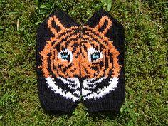Tiikerien pohjaväriksi kannattaa valita mahdollisimman tumma sävy, jotta pitkät lankajuoksut eivät erotu työstä. Lapasissa on kiilapeukalo, ja tiikerin silmien alue tehdään jälkikäteen silmukoita jäljentämällä.