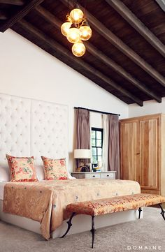 Exposed ceiling beams in bedroom with modern lighting, tufted white headboard, and neutral curtains