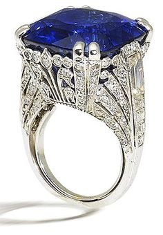 Ornate sapphire and diamond ring, by Chantecler.   Set with a cushion-cut sapphire, weighing 36.83 carats, to a single-cut diamond-set gallery with pierced foliate detailing, between collet-set baguette-cut diamond-set shoulders, mounted in platinum, the diamonds estimated to weigh approximately 3.00 carats in total, maker's case, ring size 5¼ (with sizing bar). Via Diamonds in the Library.