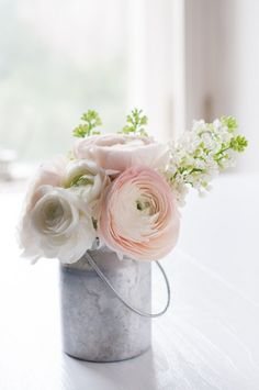Eine kleine Milchkanne mit Blumen in pastelligen Farben passt perfekt zu einer Tischdeko im Vintage-Stil.