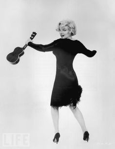 Marilyn Monroe looks over her shoulder and shimmies while holding a ukulele in a promotional portrait for director Billy Wilder's film, 'Some Like It Hot'.