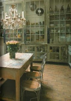tall glass doored apothecary cabinets in casually opulent large kitchen with brick floor and weathered dining table