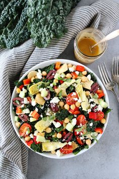 Mediterranean Kale Salad with chickpeas, tomatoes, cucumber, red pepper, artichoke hearts, olives, feta cheese, pita chips and a simple hummus dressing.