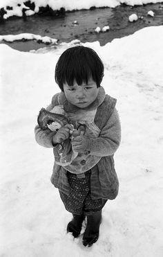 1956年、あかぎれの手で人形を抱く女の子。