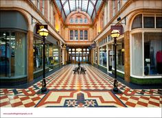 """Miller Arcade in Preston is a flamboyant High Victorian shopping Arcade of the sort found in the West Riding of Yorkshire or Manchester. The delicate iron-and-glass roof and lamp fittings,the old shop signs,lush terracota moulding,terazzo floors,benches for the flaneurs and the sense of slight rafishness..."""""""