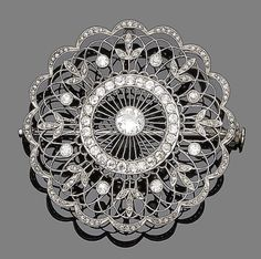 A belle époque diamond brooch/pendant, circa 1910  The finely pierced circular plaque set throughout with old brilliant and rose-cut diamonds, old brilliant-cut diamonds approx. 1.80ct total, later brooch fitting, diameter 4.9cm
