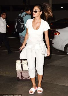 Summer fun: The X Factor judge dressed for comfort in head to toe white as she wheeled her luggage through arrivals