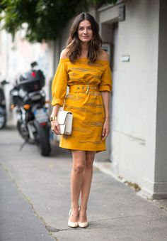 Milan Fashion Week spring 2014, Street style. Yellow off-the-shoulder dress with pattern and big buckled belt, white clutch and white heels.