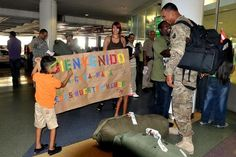 Spc. Orlando De Jesus, of the Puerto Rico Army National Guard 130th Engineer Battalion, reads the banner prepared by his children at the Luis Muñoz Marin International Airport in San Juan, Puerto Rico, on Jan 13., after returning home from his tour in Afghanistan. De Jesus is one of the many members of the PRARNG who has served in the Global War on Terrorism during Operation Iraqi Freedom and Operation Enduring Freedom. De Jesus returned from his tour in Afghanistan and is expected to re...
