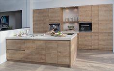 Moderne keuken met houtstructuur. Deze moderne keuken straalt één en al warmte en gezelligheid uit door het gebruik van houtstructuur in de keukenkasten en kookeiland. Alle keukenkasten zijn laminaat, greeploos en symmetrisch opgesteld. Door een gelijk aantal kasten te creëren langs beide kanten van het open gedeelte aan de wand wordt er perfecte symmetrie bekomen. Dit wordt nog meer benadrukt door de ingebouwde keukentoestellen. Het witte werkblad en de witte muren zorgen voor een mooi…