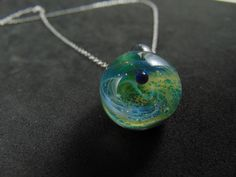 Tiny green galaxy pendant necklace for women and men, Silver fumed Borosilicate space necklace, with a floating opal planet, Glass Pendant Handmade Beads, Handmade Items, Green Galaxy, Green And Purple, Glass Pendants, Opal, Pendant Necklace, Chain, Silver