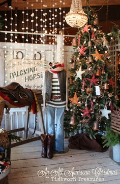 """An All American Christmas 2015"" @ Timeworn Treasures featuring velvet stars with a worn vintage look, equestrian inspired apparel, American flag infinity scarf, antique Farm sign, so much more!!! Stop in!! Christmas window display, retail display inspiration, Christmas tree, Vest, striped shirt, cowboy boots, unique holiday finds, Snowball garland"