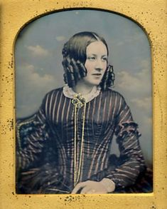 Hand-tinted daguerreotype portrait of a young woman posed in front of a cloud backdrop, circa 1850s.