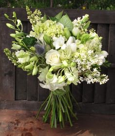 I like the variety in this arrangement. with the tiny pop of purple. white wedding flowers