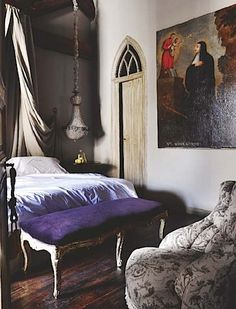 Neoclassical bedroom with arched window over the door, Christian-themed painting, canopy draping over the bed, and a velvet purple bench