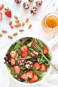 This beautiful Spring Berry Salad with Almond-Cranberry Crusted Goat Cheese is studded with strawberries and served over baby greens, but you can use any seasonal berries or a combination of berries i