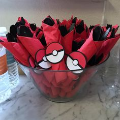 Napkins and plastic cutlery wrapped with a Poke Ball for a Pokémon-themed birthday party. Click or visit FabEveryday.com to see details and DIY instructions for a Pokémon or Pokémon Go themed kid's party, including printables, food, decorations, favors, and party activities.