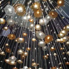 An elegant, large scale, bespoke chandelier installation of hand blown Bohemian glass with fibre optics 500x400cm mirror finish base installation Balloon Ideas, Hotel Lobby, Light Installation, Home Interior Design, Light Fixtures, Bespoke, Unicorn, Balloons, Scale