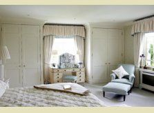 Fitted, painted wardrobes in a Hallidays bedroom scheme, with matching radiator cover
