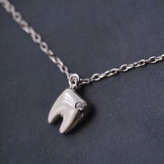 Work in the dental field? Then this beautiful tooth necklace is for you! Crafted with rhodium plated sterling silver, this gleaming necklace is adorned with quality zirconia stone. Dental World, Dental Life, Dental Art, Tooth Extraction Care, Tooth Extraction Aftercare, Teeth Implants, Dental Implants, Dental Surgery, Dental Jewelry