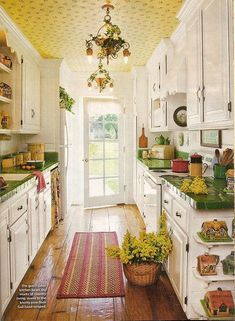 Vintage galley kitchen with green tile counter tops, yellow wallpaper on the ceiling, wide board floors, vintage green and yellow canisters...great cottage kitchen!