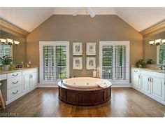 2670 Treasure Lane, Naples, FL 34102 | Large master bathroom with dual vanities, wood floors and a round soaking tub.  Balcony outside.  In the Port Royal neighborhood.