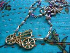 Colar confeccionada em metal dourado com contas plásticas nas cores bege perolado e roxo pingente de bicicleta em metal. R$32,90