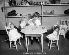 Little girl having a tea party with her dolls. 1920s.