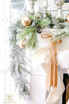 Elegant fireplace mantel decorated for Christmas with flocked evergreens and ruffled stockings. white, neutral, beautiful