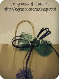 Pacco regalo con nastro di rafia blu, juta verde e fogliolina di edera