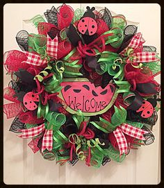 Enjoy Summer with this Welcome Watermelon Wreath handing in your home or on your front door.  It shows with red, black and lime deco mesh. There is a slice of watermelon which has been handcrafted from wood and place in the middle of the wreath. It shows with black glittered seeds and decorative paper. Letting everyone know they are welcome to come on in.  There are three cute poke a dot lady bugs that are flying all around. Black, lime and red picnic ribbons with lime glittered springs has…
