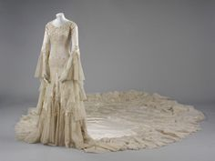 Wedding dress: Date:1933 (made)  Artist/Maker:Hartnell, Norman, born 1901 - died 1979 (designer)  Materials and Techniques:Embroidered silk satin with pearl and glass beads and satin appliqué, tulle with metal wire, trimmed with wax. Sideway