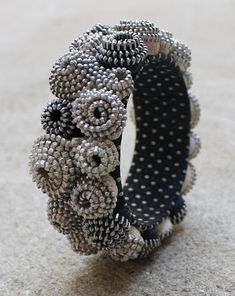 Made with many zippers.  Since I love seed beads I would make spiraling clumps of seed beads to do the same rosebud/flower look.  But, very clever with the zippers.