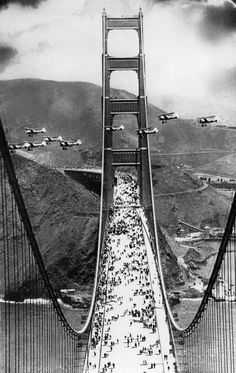 1937, military biplanes fly between the towers of the Golden Gate Bridge