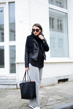 Retro dark sunglasses + leather jacket + grey pants + neutral sneakers
