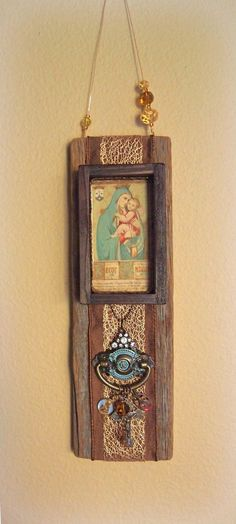 This rustic wall hanging features a 120 year old Portuguese antique holy card depicting Our Lady of Carmel. Layered over the weather-beaten barn wood are gorgeous ribbons and two vintage Catholic medals.