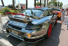 Sparkling: A young boy admires a shiny silver Porsche 911 GT2 complete with eye-catching red alloys. It is one of many luxury vehicles delivered to Cannes from Kuwait