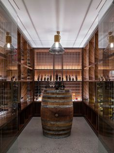 This custom wine cellar features a barrel as a table and hidden lighting to show off the bottles.