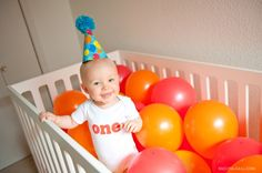 celebrating turning one with a balloon-filled crib