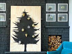Parecido com o painel, este projeto é o mais avançado: você vai precisar de uma placa de madeira, tinta ou spray preto para fazer o formato da árvore e pregos para pendurar os ornamentos. A ideia é do Dan's Lake House (em inglês).