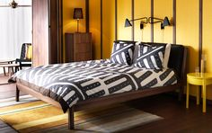 STOCKHOLM bed in stained ash with dark brown leather cushions and yellow bedside table
