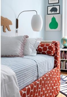 Custom upholstered day bed in burnt orange fabric with light blue walls.