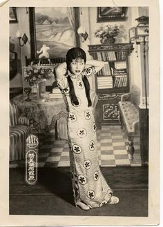 Actress dressed in floorlength cheongsam adjusts her hair /  Digital Archive of Chinese Theater in California[between 1920 and 1929] (issued)