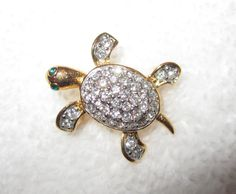 """One of almost 40 pins we bought at the Joan Rivers' estate auction--these were her favorite pins that she actually wore, from her personal jewelry box! A wonderful gift or treat yourself to a piece of history from a true queen of comedy and wonderful designer.  The baby turtle. Gold tone and encrusted with white crystals. Green crystal eyes. Approximate measurements: 1"""" x  3/4"""".  Condition: superb!"""