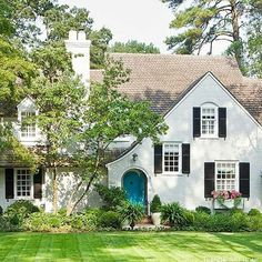 Amd my obsession with white houses and black shutters continues.   Such curb appeal with that sloped roofline, turquoise door and darling window box full of pink blooms.