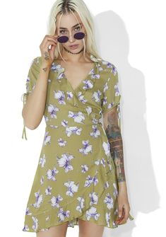 Sweet Pea Floral Wrap Dress has got our hearts in a tizzy, bb~ This sweet 'N soft mini dress features a fluttery green construction with purple flowers all over, ruffled trim, v-neckline, tied cap sleeves, and wrap style tie closures.