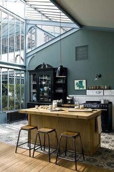 La cuisine occupe une grande partie de la pièce à vivre. Elle est délimitée par d'anciennes tommettes en ciment chinées ; îlot central réalisé sur mesure, La Maison Belle à Lyon, grand vaisselier noir, Le Grenier à Roubaix, et cuisinière, Aga.    En savoir plus sur http://www.cotemaison.fr/loft-appartement/diaporama/vivre-a-paris-autrement_18498.html?p=9#6IZlcDt1MY41Tsif.99