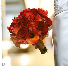 burnt orange calla lilies, deep red dahlias, roses and oncidium orchids with rosemary accents.